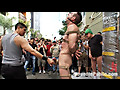 Muscle slave is stripped naked, used and humiliated while hordes of people take photos.